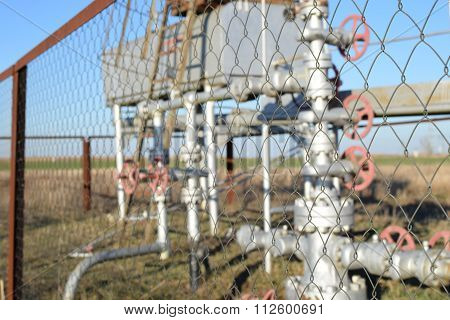 Grid the chain-link near an oil well. Shutoff valves and service equipment.
