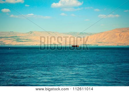 Brown wooden boat sailing in Sea of Galilee