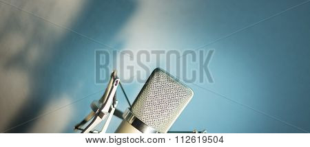 Audio recording vocal studio voice microphone with anti shock mount and built in anti pop filter for singing and voiceover actors doing voiceovers. poster