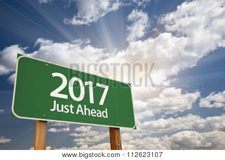 2017 Just Ahead Green Road Sign Against Dramatic Clouds and Sky.