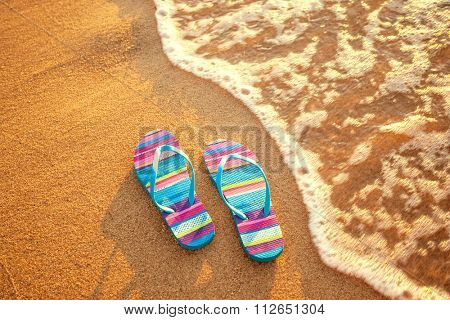 pair of flip-flops on a sandy beach at sunset, holiday and vacation concept