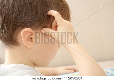 Little Boy Thinking And Scratching His Head