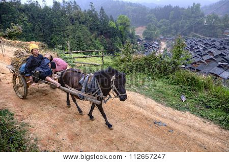 Horse Carries Wagon With Asian Peasants, Women Farmers And Child.