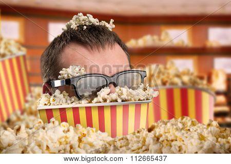 Man in glasses in a bucket of popcorn