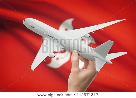 Airplane In Hand With Flag On Background - Hong Kong