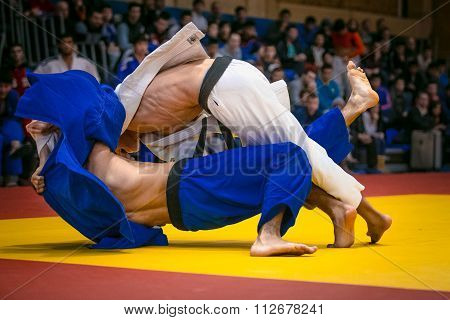 wrestling match between young male judokas on tatami. in background fans