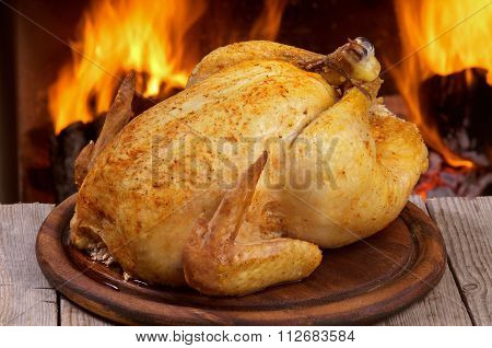 Baked chicken on wooden table.