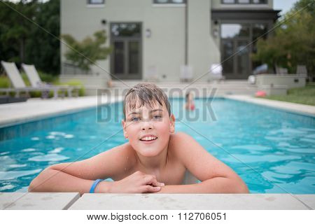 Boy is clinging to the edge of the pool at the autumn day.