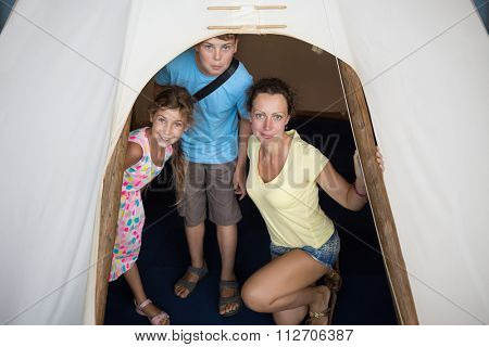 Family of three are standing into tepee in National Museum of the American Indian.