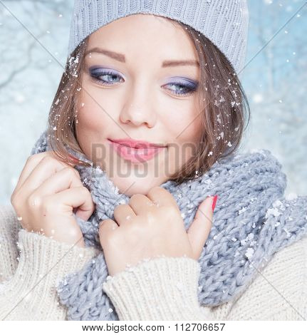 Beautiful happy smiling young woman wearing winter hat covered with snow flakes. Christmas portrait concept. Winter landscape background