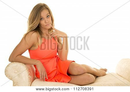 Woman In Red Dress Sit On White Sofa Finger By Mouth