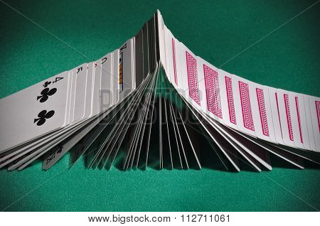 Poker playing cards turning face-up sequentially like dominoes