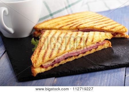 Sandwiches with ham, cheese, lettuce, grilled toasts, and a cup of coffee