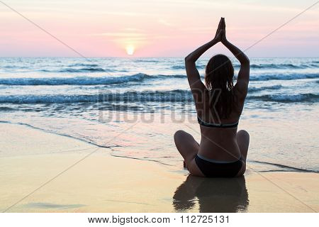 Young healthy woman practicing yoga on the beach at amazing sunset.