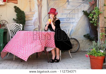Blond Lady Drinking A Cocktail In Open Air Cafe