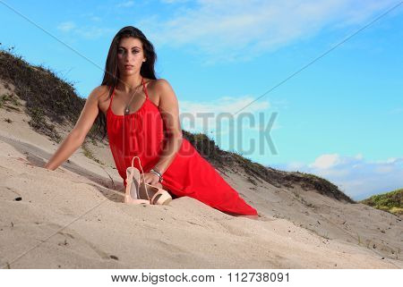 Brunette In Red Dress Resting On The Beach