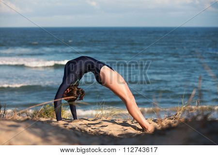Acrobatic Gymnast Is Arching Her Back On The Beach