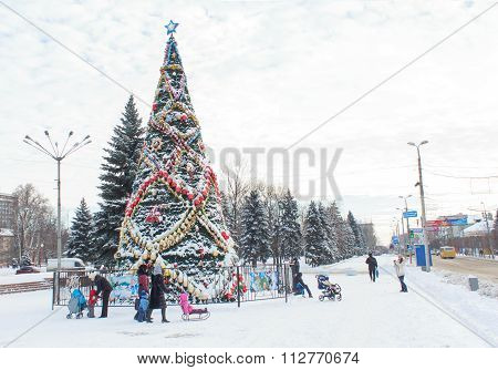 Makeevka, Ukraine - December 29, 2015: Citizens in the central square near the Christmas tree