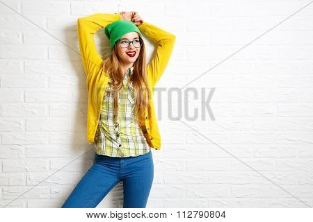Smiling Hipster Girl at White Brick Wall Background