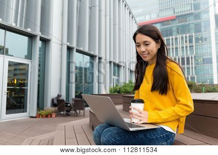 Asian Woman enjoy working at outdoor with laptop computer and coffee