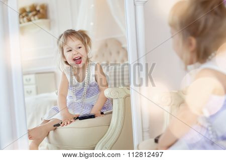 Cute little girl in her mother's room, using makeup to imitate adults