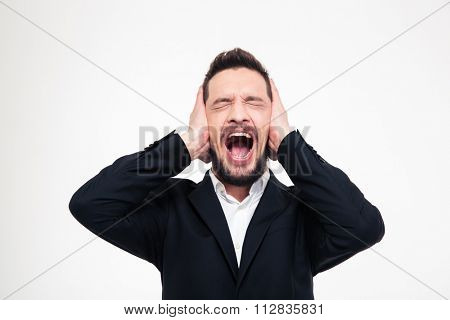 Angry businessman covering his ears and screaming isolated on a white background