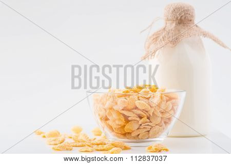 Milk and bowlful of corn flakes on white surface.