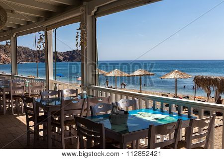 View Of A Tavern And Tourists Enjoy The Clear Water Of The Beautiful Beach In Milos Island, Cyclades