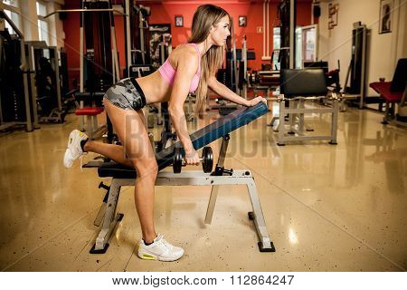 Young beautiful woman workout in fitness gym. Training body building for bikini fitness category com