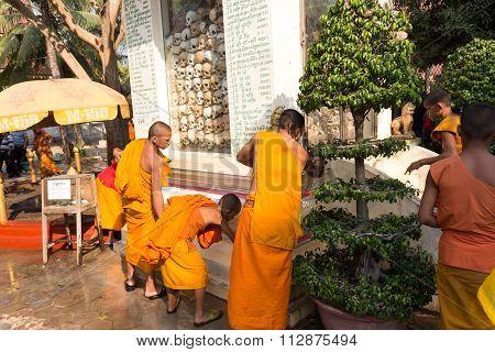 Monk Cleaning Graveyard Pile Of Skulls