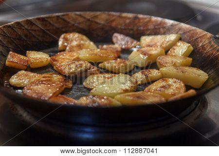 Crispy brown chip potatoes in iron frying pan