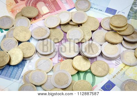 Different euro coins on different euro banknotes