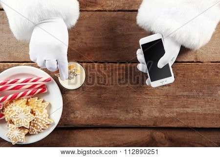 Santa Claus's hands with cellphone, glass of milk and plate of candies on wooden background, close up