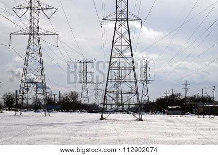 Power lines bring electricity to Joliet, Illinois and surrounding suburbs.  In the distance, one may see emissions from the smokestacks of the Joliet 29 Coal-Fired Power Generating Station in Rockdale. poster