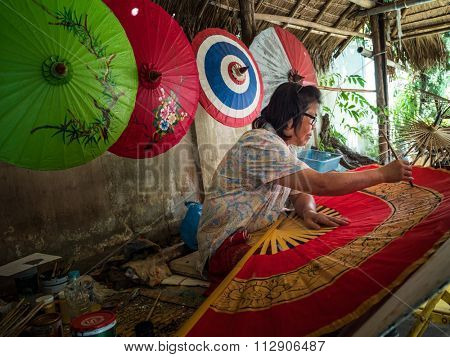 CHIANG MAI, THAILAND - NOVEMBER 22, 2015: An unidentified woman paints on a giant fan in cottage factory in Chiang Mai, Thailand. This is a traditional craft that attracts local and foreign visitors.