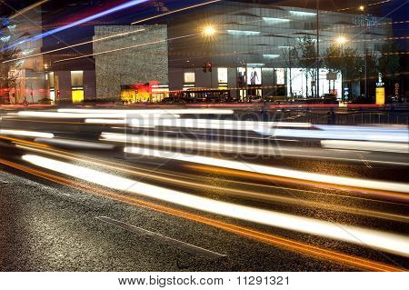 High-speed vehicles bright light trails on urban roads at night poster