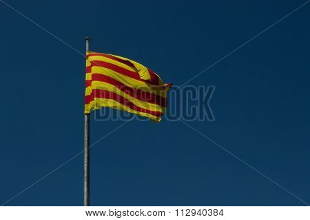 Flag of Catalonia against a blue sky at summer day