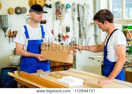 Two Worker With Cardboard In A Carpenter's Workshop
