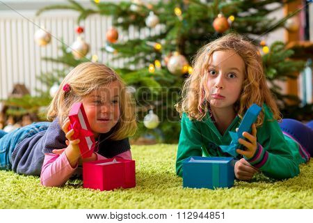 Two Disappointed Girls With Christmas Presents