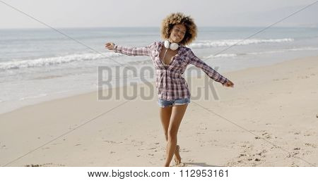 Woman on beach listening to music on smart phone happy dancing.