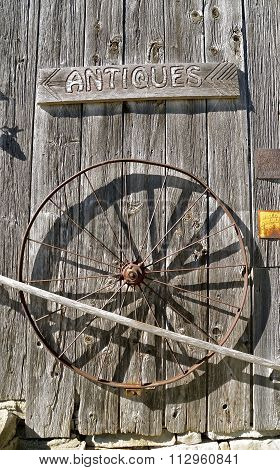 Old wheel on weathered wood siding