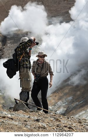 Tourists (Man And Woman) On Crater Active Volcano