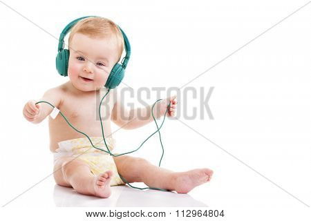 Happy baby with headphones listening to music on white background