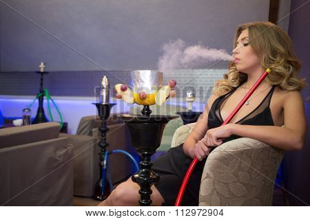 Girl in black dress with decollete exhale smoke on the hookah room