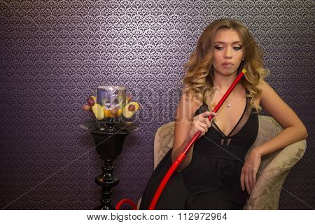 Beautiful girl in black dress with decollete in the hookah room