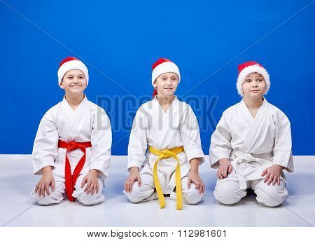 Children in cap  Santa Claus sitting in pose karate