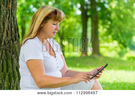 50 Year Old Woman With A Tablet In The Summer Park