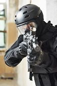Military industry. Special forces or anti-terrorist police soldier, private military contractor armed with with machine gun ready to attack during clean-up operation poster