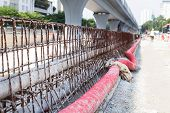 PVC and corrugated plastic pipes and rebar concrete divider in road construction site poster