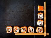 Traditional Japanese food - sushi, rolls and chopsticks for sushi on a dark background. Top view poster